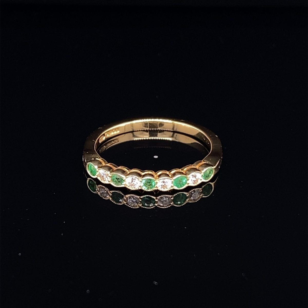 Emerald and diamond half eternity ring