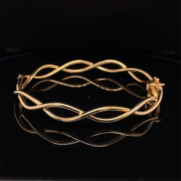 Gold oval cross over hinged bangle
