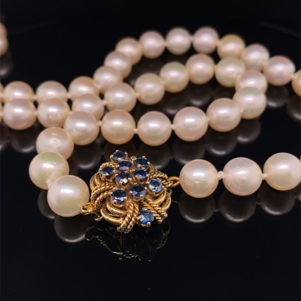 Single row of opera length pearls with yelllow gold and sapphire clasp