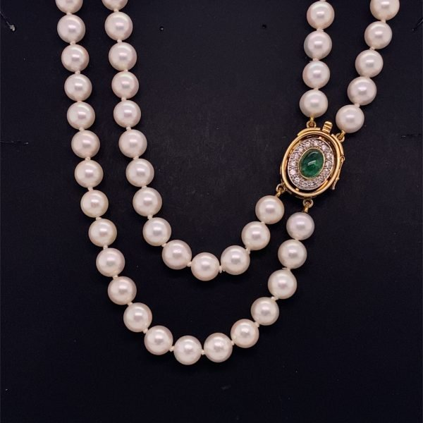Double row cultured pearls with emerald and diamond set clasp